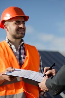 Brygadzista w pomarańczowym kasku i kamizelka trzymająca dokumenty do podpisu.