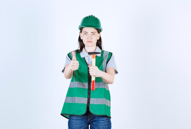 Brygadzistka robi znak ręką trzymając młotek przed szarą ścianą
