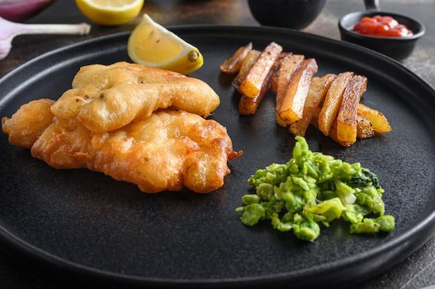 Brytyjska tradycyjna ryba z frytkami z puree z groszku miętowego, sos tatarski pionowy widok z boku na czarnej płycie bliska szczegóły widok z boku. nad starym rustykalnym stołem.