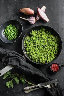 Brytyjski groch papkowaty gotowane patelni i grochu w misce z miętą szalotka pieprzem i solą na czarnej powierzchni kamienia ekologicznej żywności keto widok z góry z widelcem i nożem.