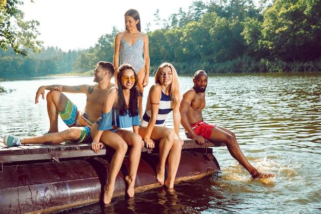 Bryzganie wody i śmiech na molo na rzece