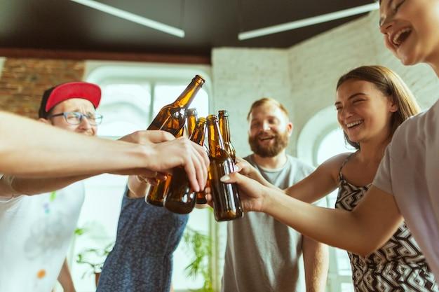 Brzęczące butelki. młoda grupa przyjaciół pijąca piwo, bawiąca się, śmiejąca się i świętująca razem. kobiety i mężczyźni w szklankach piwa. oktoberfest, przyjaźń, wspólnota, koncepcja szczęścia.