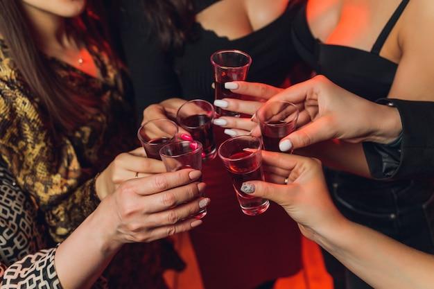 Brzęczące szklanki z alkoholem i opiekanie