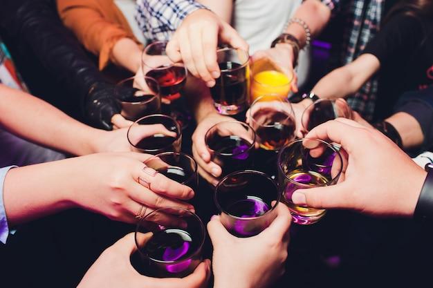 Brzęczące szklanki z alkoholem i opiekaniem, impreza. gratulacje dla wydarzenia. wesoła impreza przyjaciół.
