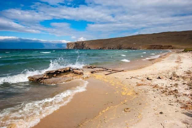 Brzeg jeziora bajkał z rozbryzgami fal rozbijających się o kamienie. piaszczysty brzeg i skalny przylądek w oddali