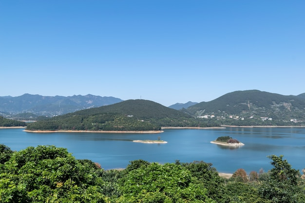 Brzeg jeziora jest zielony, w centrum jest kilka małych wysepek, a niebo i woda są niebieskie