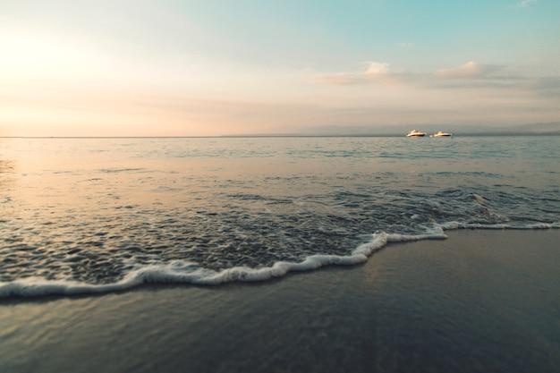 Brzeg lazurowego morza podczas zachodu słońca