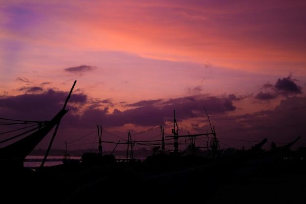 Brzeg oceanu o zachodzie słońca sylwetki łodzi i ludzi