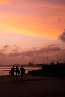 Brzeg oceanu o zachodzie słońca sylwetki łodzi i surferów ludzi iść na plażę
