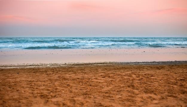 Brzeg plaży o zachodzie słońca z różowym tle nieba