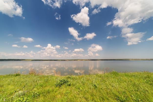 Brzeg rzeki po południu, z piękną zieloną trawą na pierwszym planie, na tle pięknego niebieskiego nieba z chmurami
