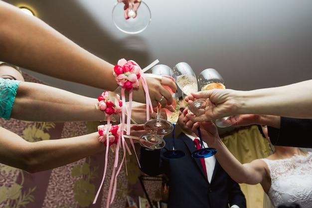 Brzęk okularów na weselu. goście weselni pijący szampana