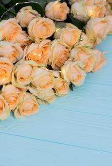 Brzoskwini róże na drewnianym turkusowym tle