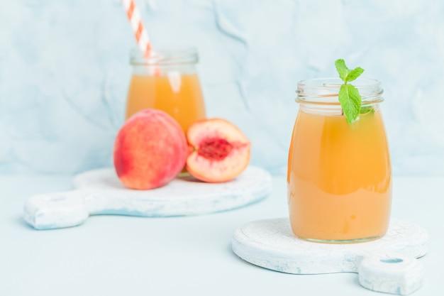 Brzoskwinia smoothie w słoikach ze świeżych dojrzałych owoców i zielonych liści mięty na niebieskim tle pastelowych