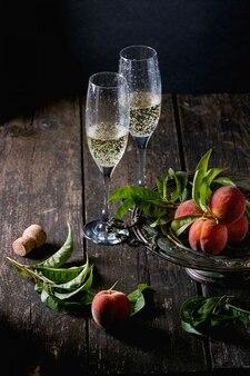 Brzoskwinie na gałęzi z szampanem