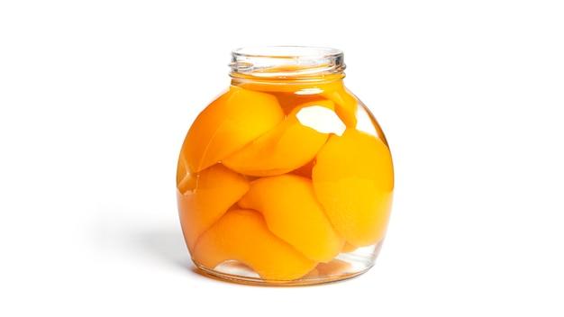 Brzoskwinie w puszce w szklanym słoju. słodkie brzoskwinie w syropie na białym tle.