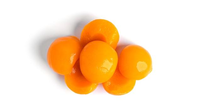 Brzoskwinie w puszkach na białym tle. słodkie brzoskwinie w syropie na białym tle.