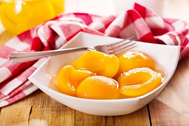 Brzoskwinie w puszkach w misce na drewnianym stole