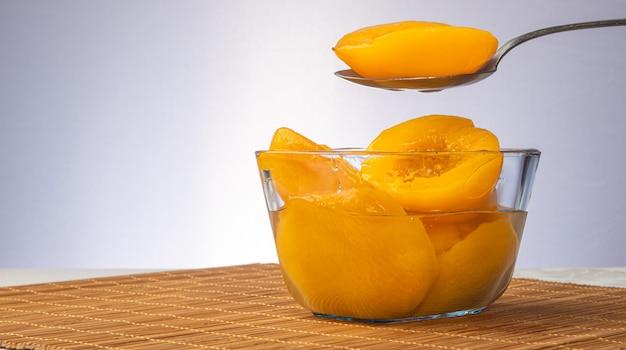 Brzoskwinie w syropie umieszczone w szklanej misce na drewnianym macie, szare tło gradientowe, selektywna ostrość.