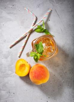 Brzoskwiniowa mrożona herbata na betonowym szarym tle z miętą i lodem, fajny napój na letni gorący sezon
