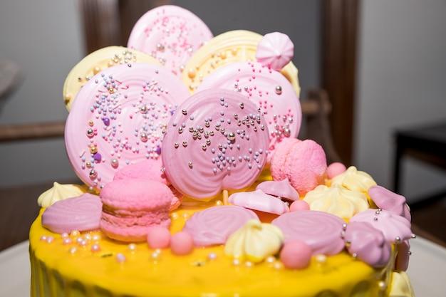 Brzoskwiniowe ciasto z bezą i cukierkami na urodziny dziecka. świąteczny stół dla dzieci, ciasto, słodycze, słodkie jedzenie. batonik.