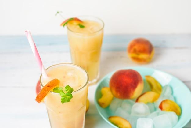 Brzoskwiniowy orzeźwiający koktajl w szklance z lodem i kawałkami owoców oraz mięty latem.