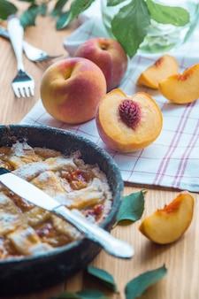 Brzoskwiniowy placek na żeliwnej patelni leży na drewnianym stole. na stole leżą pokrojone brzoskwinie, zielone liście, materiał, dwa widelce, nóż.