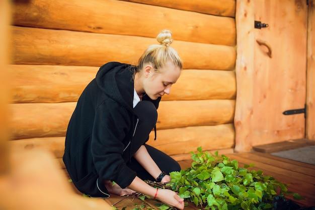 Brzozy miotły na drewnianej ścianie w rosyjskiej skąpaniu. wiele brzozowych mioteł kobieta w ogrodzie wyplata stopy do kąpieli. rosyjska wioska. prace domowe. rzemiosło ludowe.