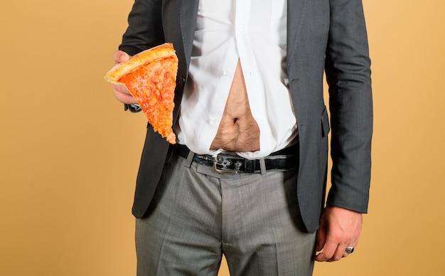 Brzuch człowieka i pizza grubas z kawałkiem pizzy w ręku otyłość koncepcja fast foodów gruby facet z nadwagą