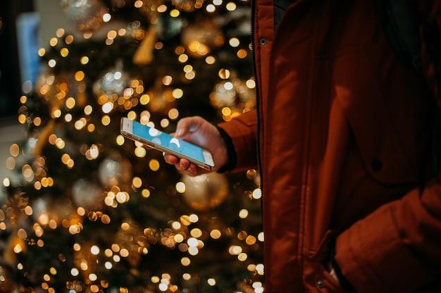 Brzuch człowieka za pomocą inteligentnego telefonu przed podświetlaną choinkę.