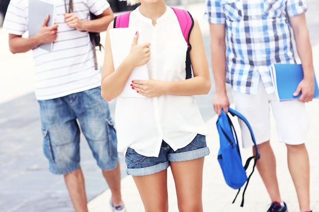 Brzuch grupy przyjaciół idących do szkoły