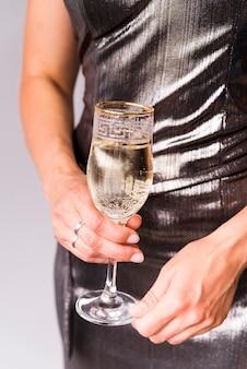 Brzuch kobiety trzyma kieliszek do szampana