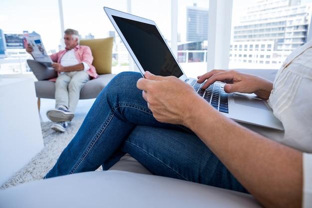 Brzuch kobiety używa laptop podczas gdy mężczyzna czyta gazetę