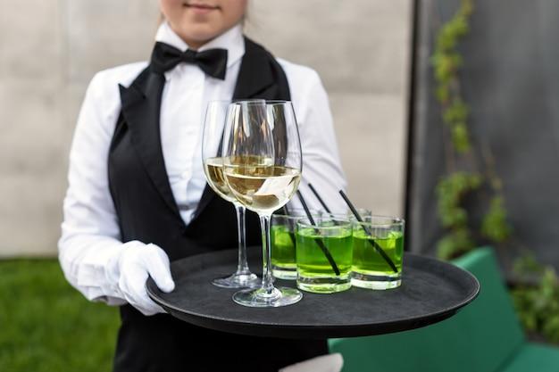 Brzuch profesjonalnego kelnera w mundurze serwującym wino podczas imprezy cateringowej w formie bufetu, uroczystości lub wesela. pełne kieliszki szampana na tacy. usługi cateringowe na przyjęciach na wolnym powietrzu, kelner na służbie.