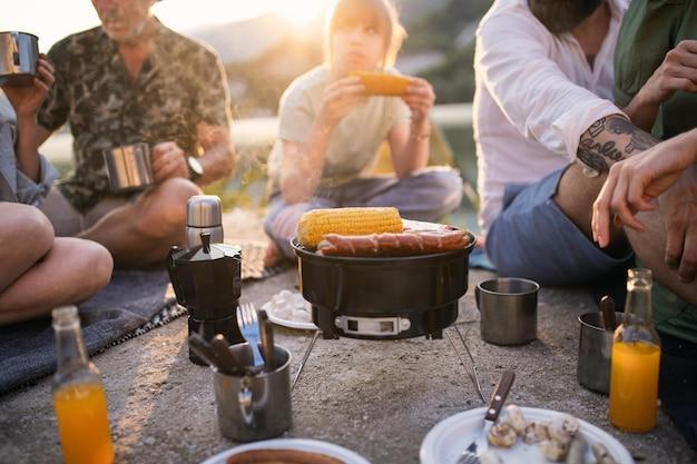 Brzuch szczęśliwej wielopokoleniowej rodziny na letnim wyjeździe, grill nad jeziorem.