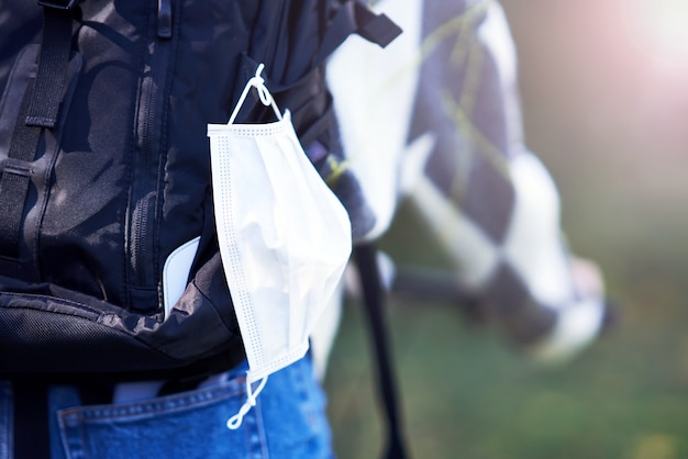 Brzuch ucznia jadącego do szkoły rowerem z maską przyczepioną do plecaka