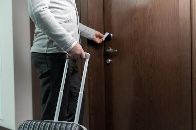 Brzuch współczesnego biznesmena lub podróżnika z walizką używającą karty do otwierania drzwi pokoju hotelowego podczas wchodzenia do niego