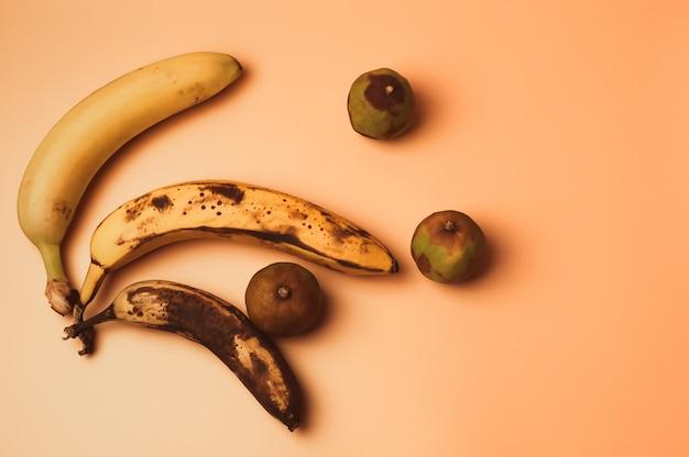 Brzydka modyfikacja owocowa bananów od dojrzałych do bardziej zepsutych brązowych z plamami i zbutwiałymi limonkami