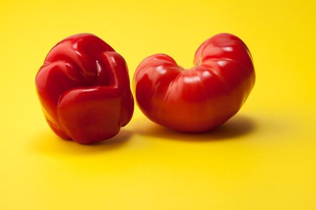 Brzydka papryka i pomidor w kształcie serca na żółtym tle.