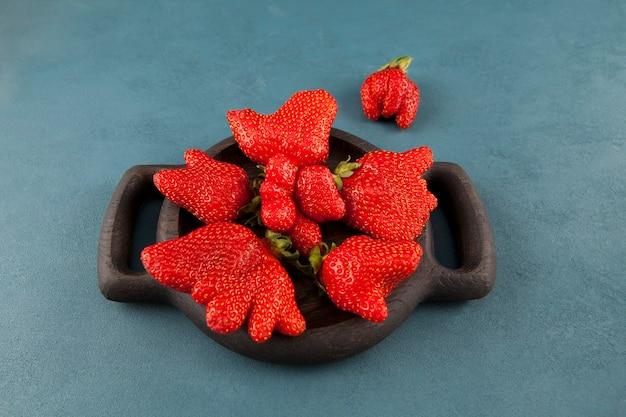 Brzydka truskawka. niezwykły kształt owoców. jagody w drewnianym talerzu na niebieskim stole. widok z góry.