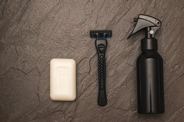 Brzytwa mężczyzny, kawałek białego mydła i spray na tle kamienia. zestaw do pielęgnacji męskiej twarzy. leżał płasko.