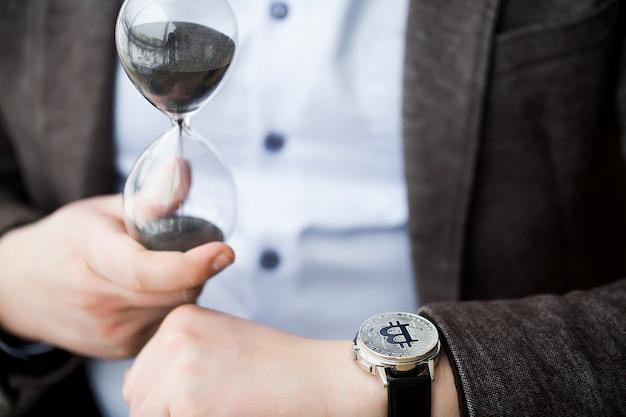 Btc. biznesmen inwestujący w bitcoin i etherium w walucie crypo, trzyma w rękach piaskowy zegar, czekając na wzrost waluty