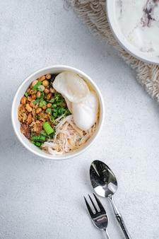 Bubur ayam, indonezyjska owsianka ryżowa z rozdrobnionym kurczakiem na białym tle