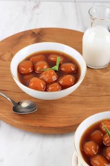 Bubur Biji Salak (candil) To Słynny Indonezyjski Deser Podczas śniadania Podczas Ramadanu. Wykonane Z Kulek Kabocha Ze Słodkich Ziemniaków Lub żółtej Dyni Z Syropem Z Cukru Palmowego I Mlekiem Kokosowym. Premium Zdjęcia