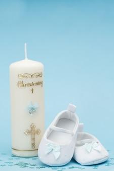 Buciki dziecięce z niebieską wstążką i świecą chrzciny