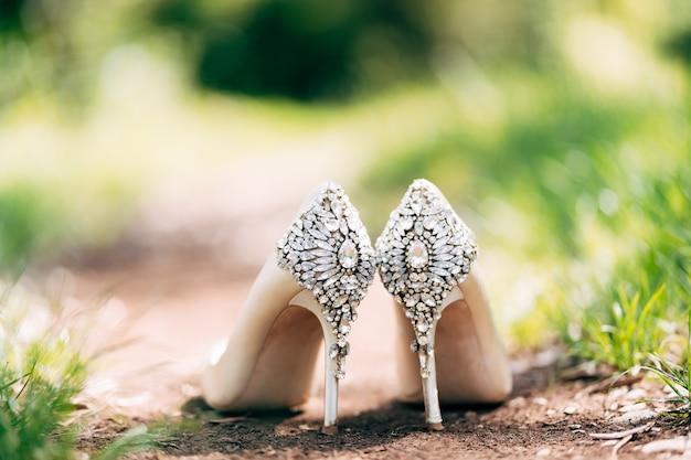 Buciki panny młodej ozdobione kryształkami stojącymi na ziemi