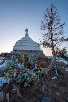 Buddyjska stupa na wyspie ogoy nad jeziorem bajkał z drzewem i wieloma wiszącymi kolorowymi flagami. zima, śnieg na ziemi. wieczór.
