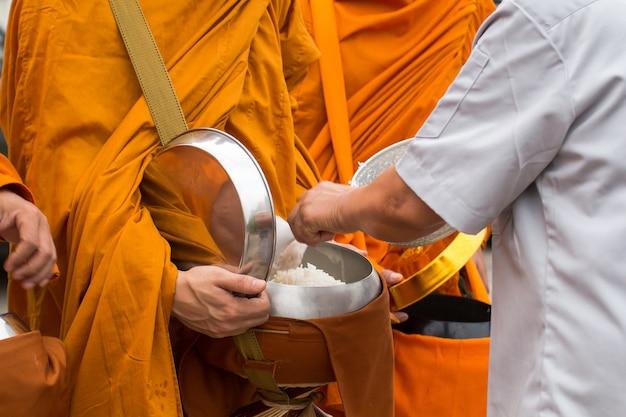 Buddyjski mnich z tajlandii, podczas gdy stoją w kolejce ludzie czekają na złożenie ofert ryżowych w swoich
