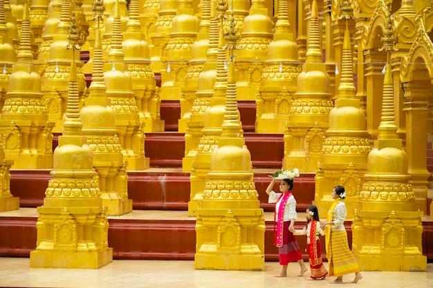Buddyści w lokalnych strojach kulturalnych podróżują, aby zasłużyć na to, po drodze jest wiele złotych pagód.