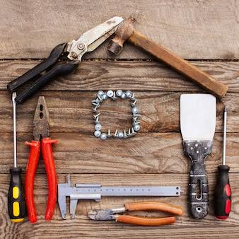 Budów narzędzia w postaci domu na drewnianym tle.